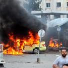 A car is left in flames at the scene where suicide bombers blew themselves up at a bus station during morning rush hour in the coastal town of Tartus, Syria. Photo: Sana/AP
