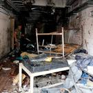 A Syrian Army soldier inspects a damaged emergency room inside National Hospital after explosions hit the Syrian city of Jableh