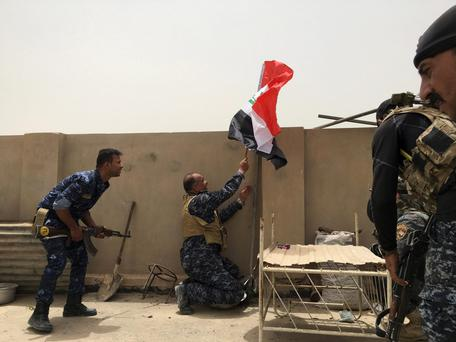 Iraqi security forces rise a national flag during house to house fighting against Islamic State militants in central Fallujah