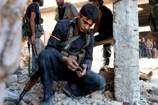 A rebel fighter reloads during clashes with state forces in Aleppo