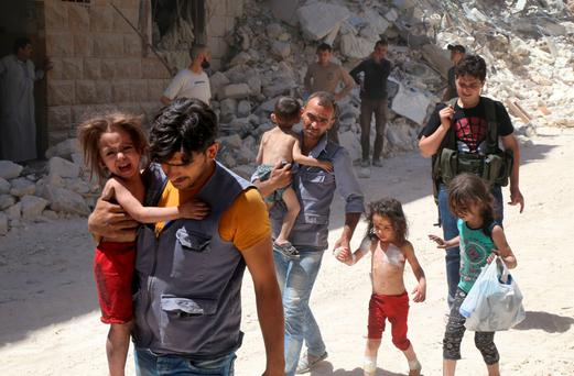Syrian men carry injured children away from rubble in Aleppo. Photo: Getty