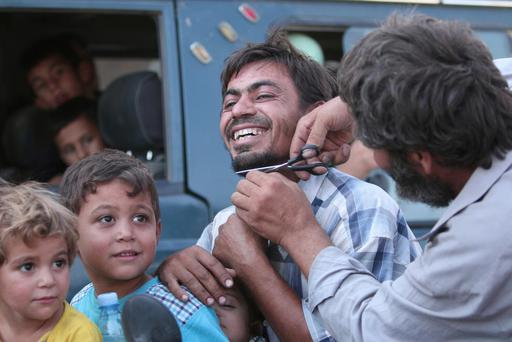 A man cuts the beard of a civilian who was evacuated from IS control Photo: REUTERS/Rodi Said