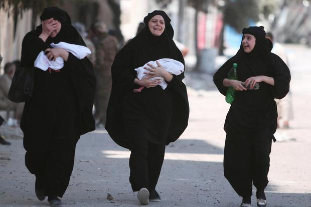 Women carry newborn babies while reacting after they were evacuated Photo: REUTERS/Rodi Said