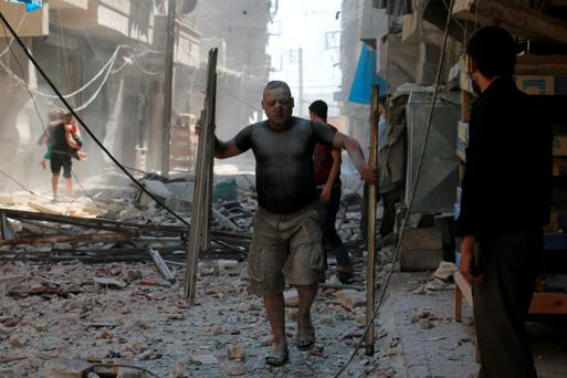 A Syrian man covered with dust on a street cluttered with rubble following a reported airstrike on a rebel-held neighbourhood in Aleppo.