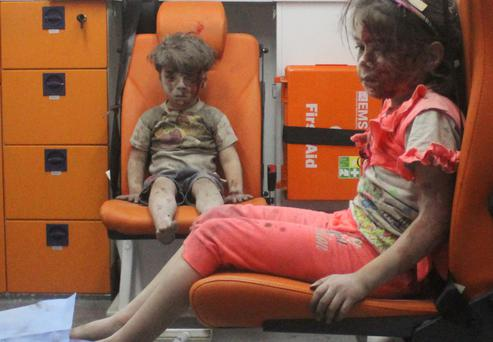 Three-yearold Omran Daqneesh, with bloodied face, sits with his sister inside an ambulance after they were rescued following an airstrike in the rebel-held al-Qaterji neighbourhood of Aleppo