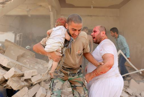A Syrian man carries a wounded child following a barrel bomb attack on the Bab al-Nairab neighbourhood of the northern Syrian city of Aleppo yesterday. Photo: Getty