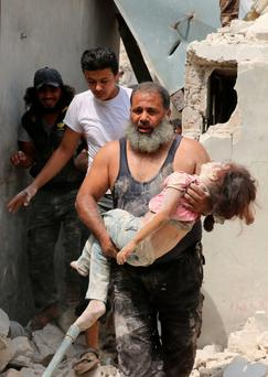 A Syrian man carries a wounded child in the rubble of buildings following a barrel bomb attack on the Bab al-Nairab neighbourhood of the northern Syrian city of Aleppo on Thursday. Photo: Ameer Alhalbiameer/Getty