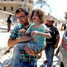 A man carries a girl that survived double airstrikes on the rebel held Bab al-Nairab neighborhood of Aleppo.