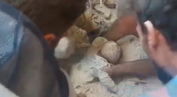 A baby is rescued from the rubble of a collapsed building in Aleppo in a still image taken from a video posted on social media Picture: Reuters