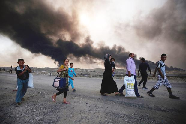 Displaced Iraqi families arrive near a checkpoint east of Mosul as they flee areas of unrest while fires burn in the background Photo: AFP/Getty Images