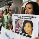 A migrant workers alliance group hold placards to protest the killings of two Indonesian women in 2014 outside the High Court in Hong Kong