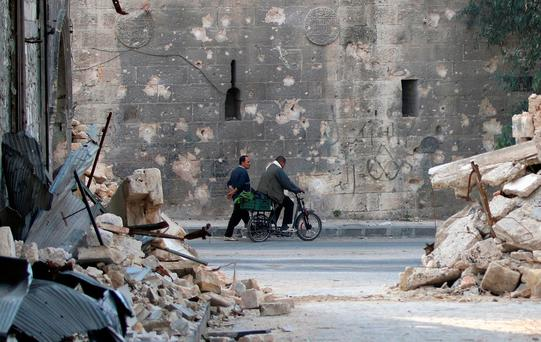 A man walks past a man riding a bicycle near the rubble of damaged buildings in the rebel held area of Old Aleppo, Syria. Photo: REUTERS/Abdalrhman Ismail
