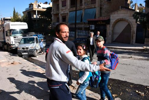 A Syrian man evacuates children from a school reportedly hit by rebel rocket fire in the Furqan neighbourhood of the government-held side of west Aleppo this week.