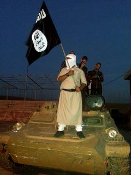 An Isil fighter holds a flag while standing on an armoured vehicle in Mosul
