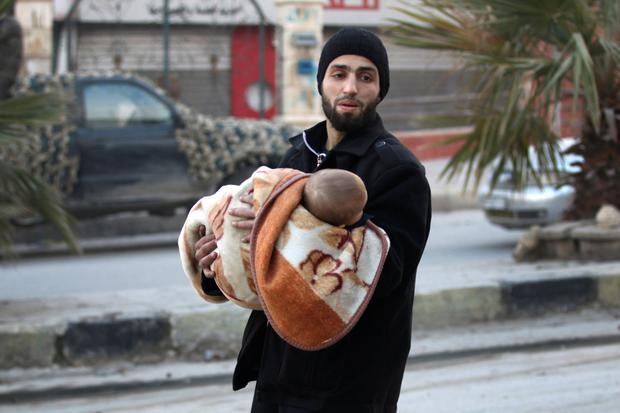 A man flees with a child deeper into the remaining rebel-held areas of Aleppo. Photo: Reuters
