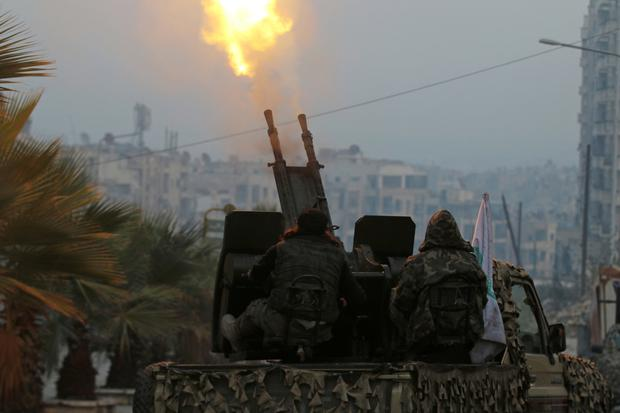 Free Syrian Army fighters fire an anti-aircraft weapon on government forces from a rebel-held area of Aleppo. Photo: Reuters