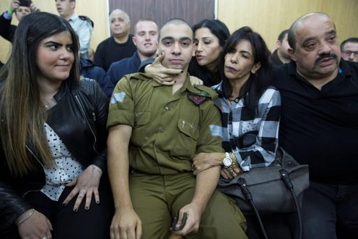 Israeli soldier Elor Azaria is surrounded by friends and family as he awaits the verdict in a Tel Aviv court