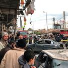 Syrian civilians and emergency services gather at the site of a car bomb explosion in Syria's coastal city of Jablah