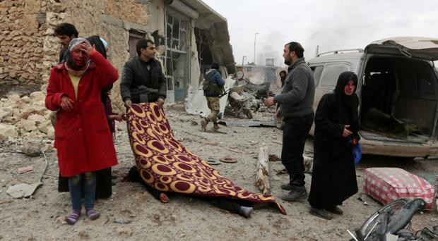An injured woman cries as a man covers a dead body after a car bomb explosion in Jub al Barazi, east of the northern Syrian town of al-Bab. Photo: Khalil Ashawi/Reuters