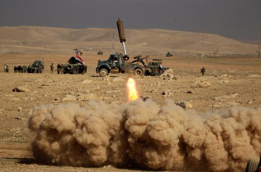 Iraqi forces fire a missile toward Isil militants during a battle south of Mosul. Photo: Reuters