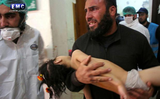 A man carries a child following the suspected chemical attack. Photo: AP