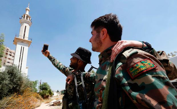 Syrian special forces take a selfie picture a mobile phone in al-Qaboun, a formerly rebel-held north-eastern suburb of Damascus, after it was retaken by the Syrian government forces yesterday. Photo: AFP/Getty Images