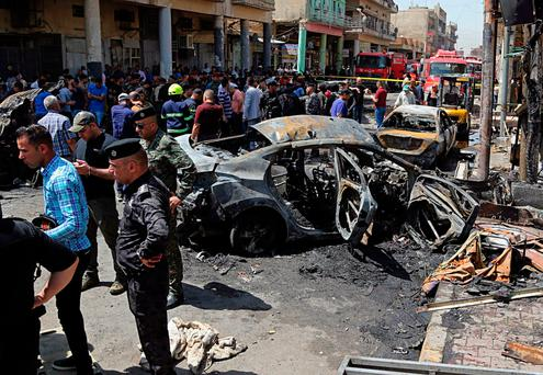 Security forces and civilians at the site of a bomb attack in Baghdad, Iraq. Another bomb exploded outside an ice-cream shop in the Karrada neighbourhood. Photo: AP/ Karim Kadim