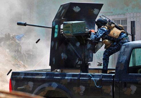 An Iraqi soldier fires a 23mm anti-aircraft gun in the Old City of Mosul yesterday. Photo: Getty