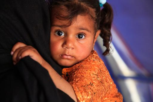 Um Jad holds daughter Suha (2) in a refugee camp near Mosul. Photo: PA