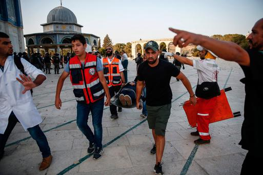 Palestinian paramedics carry an injured woman on a stretcher past the Dome of the Rock, after clashes broke out inside the al-Aqsa mosques compound in Jerusalem's Old City. Photo: AFP/Getty Images