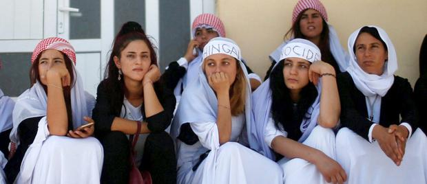 Yazidis attend a commemoration to mark three years since Isil launched a 'genocidal campaign' against them in Sinjar, Iraq