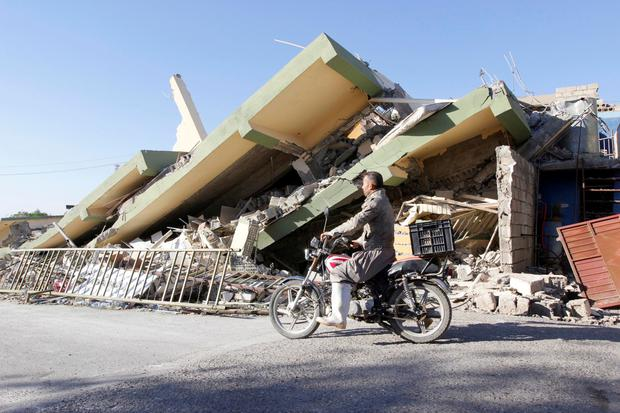 A motorcyclist rides by a damaged building in Darbandikhan, Kurdistan. Photo: Reuters/Ako Rasheed