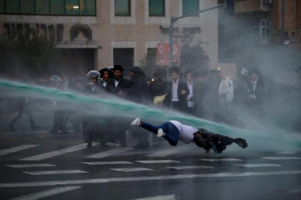 A bystander falls as Israeli police spray water cannons during a demonstration by ultra-Orthodox Jews against the detention of members of their community who failed to report to a military recruiting office in Jerusalem Photo: Reuters