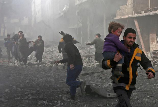 A Syrian man carries a child injured in government bombing in the rebel-held town of Hamouria, in the besieged Eastern Ghouta region on the outskirts of the capital Damascus. Photo: Getty Images