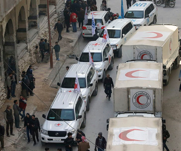 This photo released by the Syrian Red Crescent shows civilians gathering near a convoy of vehicles of the Syrian Red Crescent in Douma, eastern Ghouta, yesterday. Photo: AP