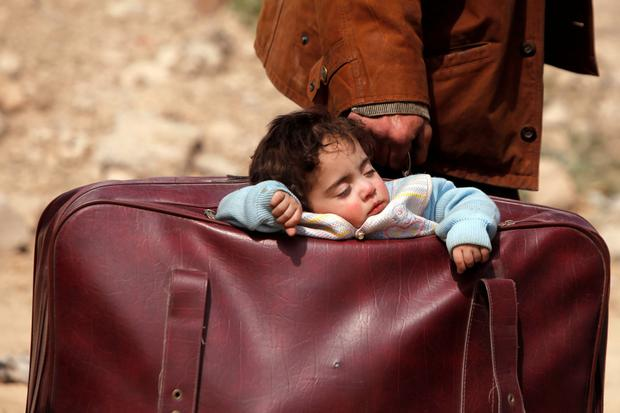 A child sleeps while being carried in a bag in the village of Beit Sawa, Eastern Ghouta, as 12,000 civilians fled along the 'humanitarian corridor' yesterday. Photo: Omar Sanadiki/Reuters