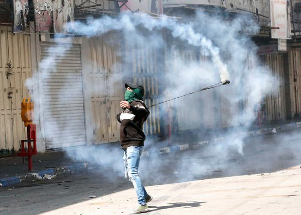 A Palestinian demonstrator throws back a teargas canister towards Israeli forces during clashes in Hebron. Photo: AFP