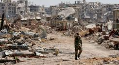 A Syrian regime member walks amid the destruction in Jobar in Eastern Ghouta, on the outskirts of Damascus. Photo: Getty Images