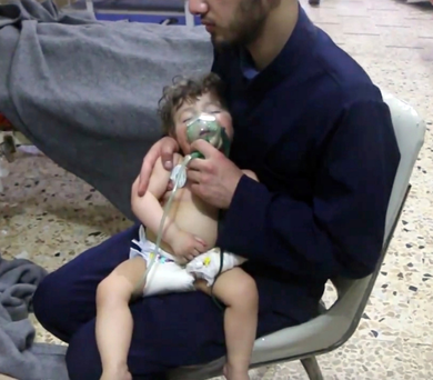 A medical worker gives a child oxygen at a makeshift medical clinic in Douma Photo: AP