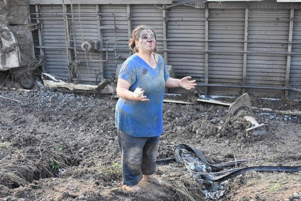 An injured woman appeals for help at the crash site in Tekirdag province, with the overturned train visible in the background. Photo: Reuters