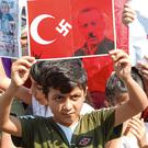 Message: A young protester holds up a banner depicting Turkish President Recep Tayyip Erdogan as a Nazi during a rally in Beirut against his government's actions in Syria. Photo: Aziz Taher