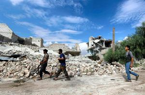 Rebel fighters carry their weapons as they walk towards their positions near Nairab military airport in Aleppo