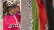 A Syrian Kurdish refugee girl from the Kobani area leans on the surrounding fence of a refugee camp in Suruc, near the Turkey-Syria border. Some 200,000 people have been forced to flee since the Isil advance