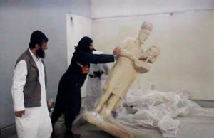 Erasing history: A militant topples an ancient artefact in the Nineveh Museum in Mosul, Iraq