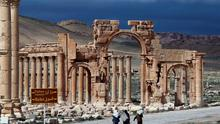 Syrian citizens walking in the ancient oasis city of Palmyra.
