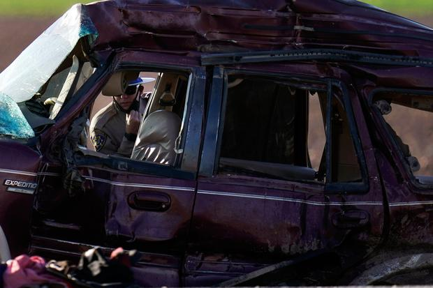 A California Highway Patrol officer examines the scene of a deadly crash in Holtville, Calif., Tuesday, March 2, 2021. Authorities say a semitruck crashed into an SUV, killing multiple people. (AP Photo/Gregory Bull)