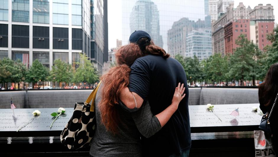 People embrace at the September 11 Memorial in New York City. Photo: Getty
