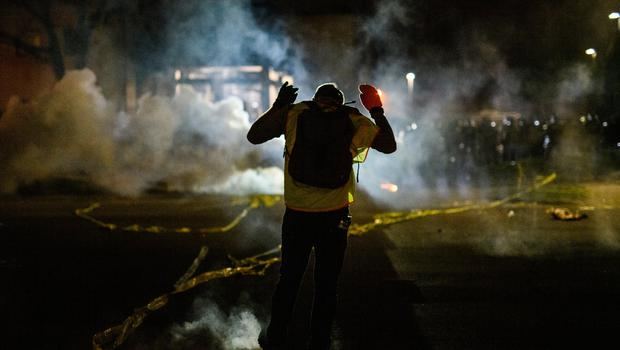 A protestor faces police lines in Brooklyn Center after Daunte Wright (20) was shot and killed. Photo: Getty
