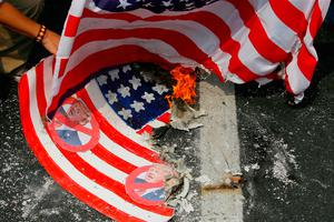 Protesters burn a mock U.S. flag and a real one during a rally at the U.S. Embassy to coincide with the inauguration of President-elect Donald Trump as the 45th President of the United States Friday, Jan. 20, 2017, in Manila, Philippines. Left-wing and Muslim activists have asked President Rodrigo Duterte in a noisy protest to keep his promise of charting a foreign policy independent of America by staying away from U.S. President-elect Donald Trump. (AP Photo/Bullit Marquez)