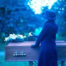 A woman placing a flower on a coffin Photo: Getty